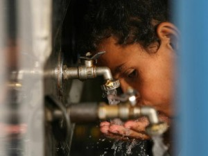 A Palestinian boy drinks water from a fa