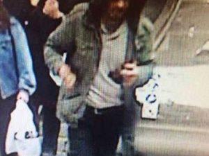 Polizia mostra la foto di un uomo con felpa e cappuccio
