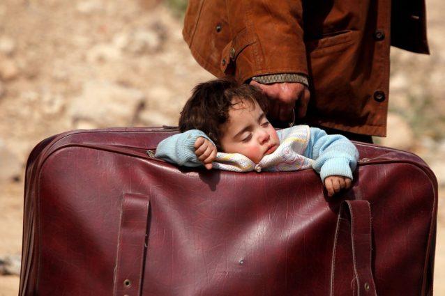 Un bimbo dorme in valigia, il simbolo degli innocenti in fuga da Ghouta Est e da Afrin