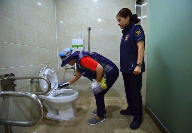 Agenti di polizia ispezionano un bagno pubblico a Seoul alla ricerca di telecamere nascoste (Gettyimages)