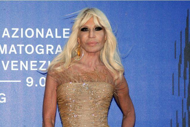 Piume e capelli al vento: Donatella Versace sfida così il maltempo a Venezia