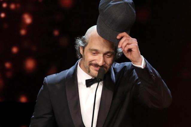 Claudio Santamaria nel momento in cui si toglie il cappello, svelando la vistosa pelata