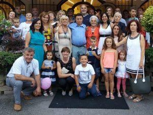 La famiglia Vallini: Augusto (camicia blu, in piedi) e Lucrecia (abito bianco, in piedi)