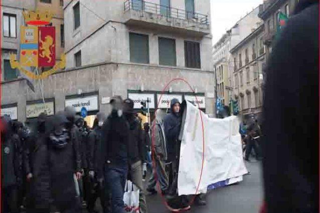 Nel cerchio il manifestante No Expo che era ricercato da tre anni, impegnato durante il corteo del primo maggio 2015 (Facebook)