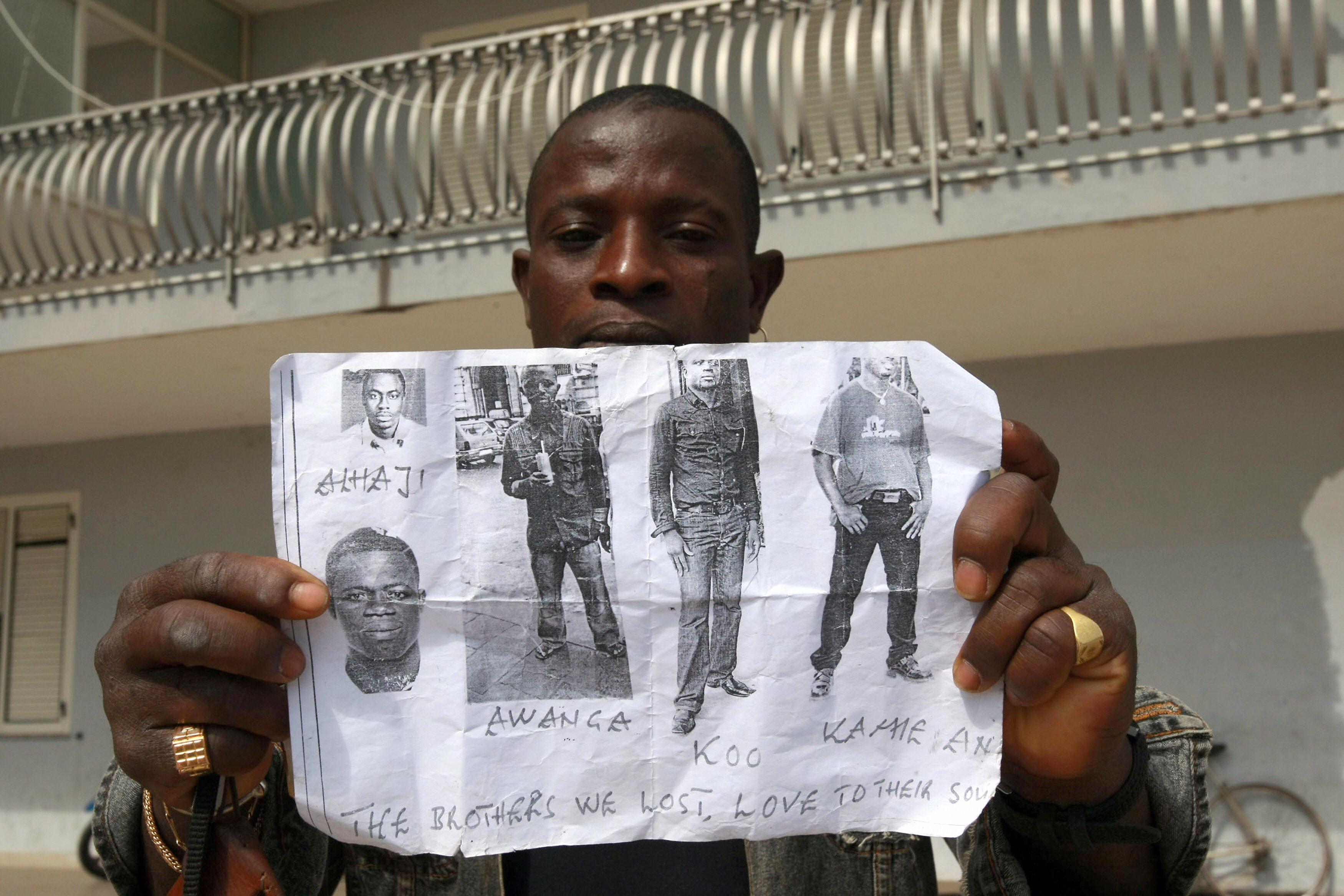 Un immigrato mostra i volti delle vittime della strage di Castelvolturno
