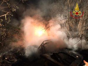 Rifiuti in fiamme su una strada, pompieri al lavoro per più